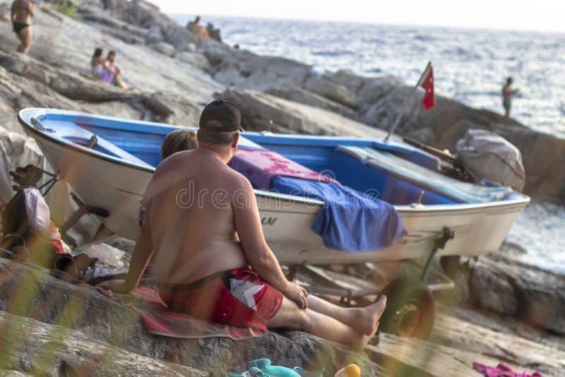 OLUDENIZ - FETHIYE, TURQUIA - 24 DE AGOSTO DE 2018 Tiro limpo dos povos que relaxam na praia no tempo do por do sol imagens de stock