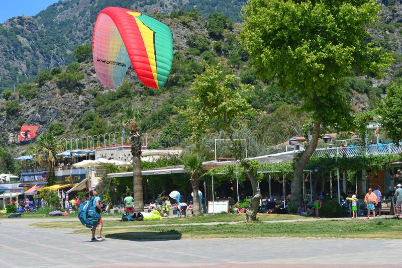 Oludeniz, Turkey - May 23, 2019: Paragliding in Oludeniz. Paraglider packs a parachute. Tourists are watching this stock images