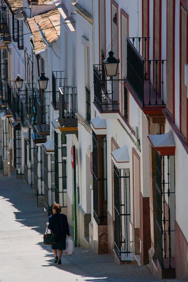Olvera Cadiz landskap, Andalusia, Spanien - mars 25, 2008: kvinna med shopping i Calle Maestro Amado arkivfoton