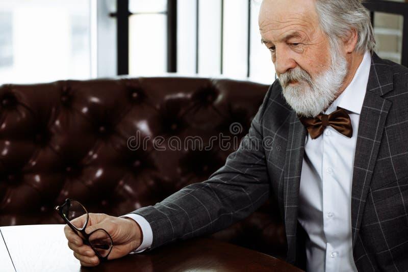 Olycklig åldring som rymmer hans exponeringsglas och sitter på den röda soffan fotografering för bildbyråer