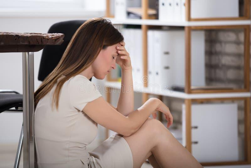 Olycklig affärskvinna Sitting In Office royaltyfri bild