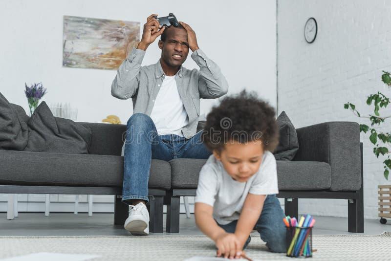 olycklig afrikansk amerikanfader som spelar videospel- och sonteckningen på golv royaltyfri fotografi
