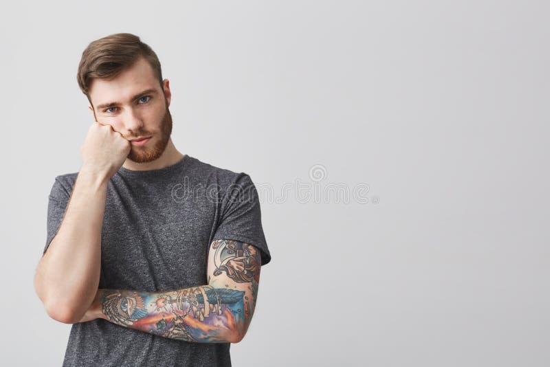 Olycklig attraktiv ung man med skägget och tatuerat huvud för arminnehav med handen, borras med lång föreläsning på arkivfoton