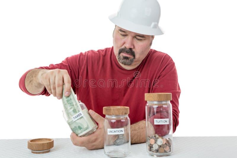 Olycklig byggnadsarbetare som betalar skatterna arkivbild