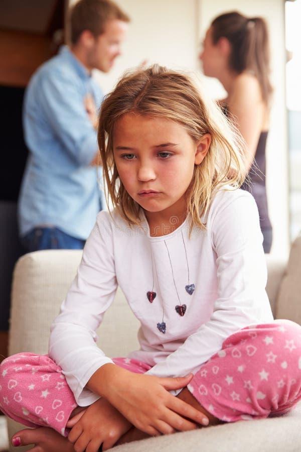Olycklig flicka hemma med föräldrar som argumenterar i bakgrund royaltyfri fotografi