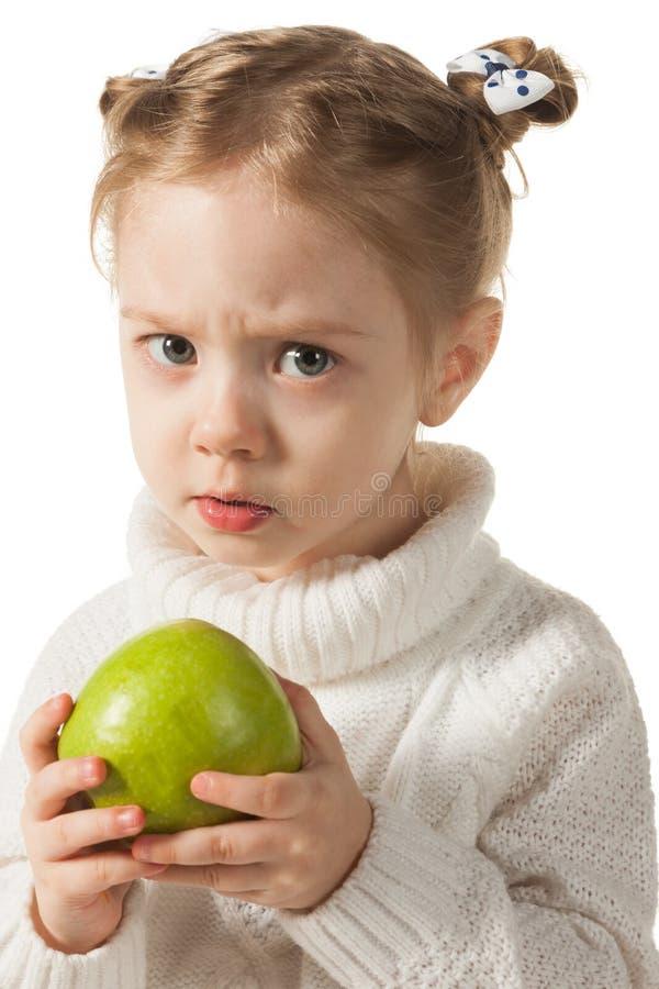 Olycklig flicka med det gröna äpplet arkivfoton