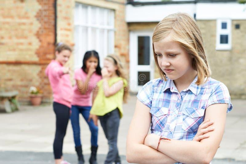 Olycklig flicka som omkring skvallras av skolavänner arkivfoton
