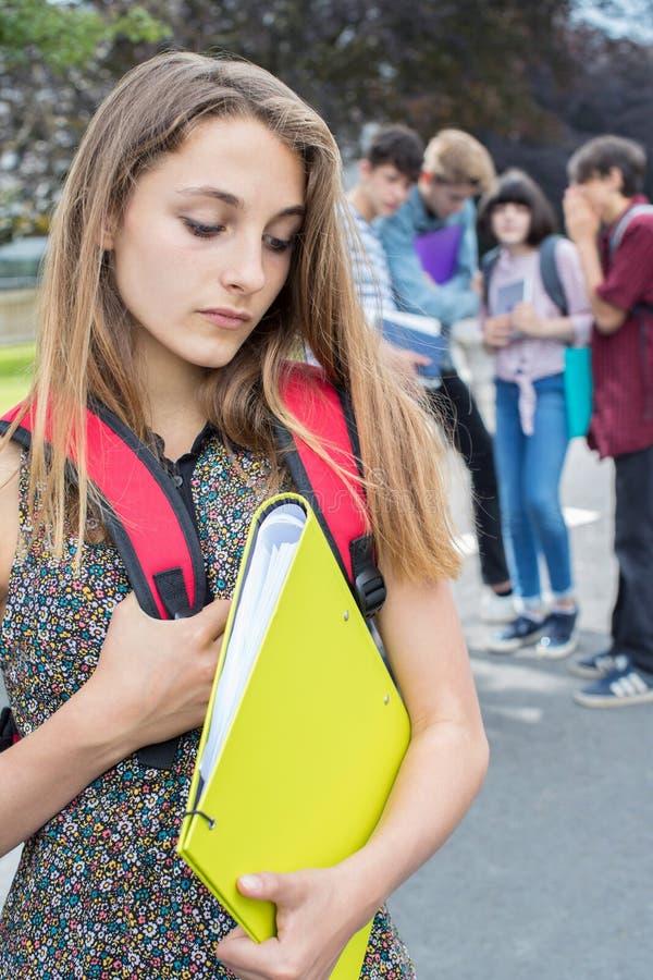 Olycklig flicka som omkring skvallras av skolavänner arkivbild
