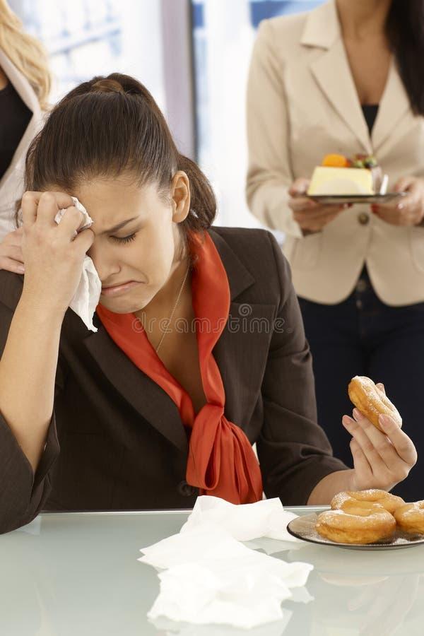 Olycklig kontorsarbetare som äter munken arkivfoto