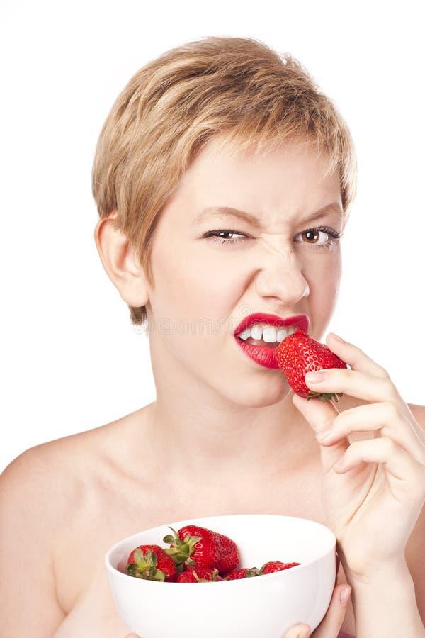 Olycklig kvinna som äter jordgubben arkivbilder