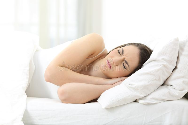 Olycklig kvinna som sover på en obekväm madrass royaltyfri foto