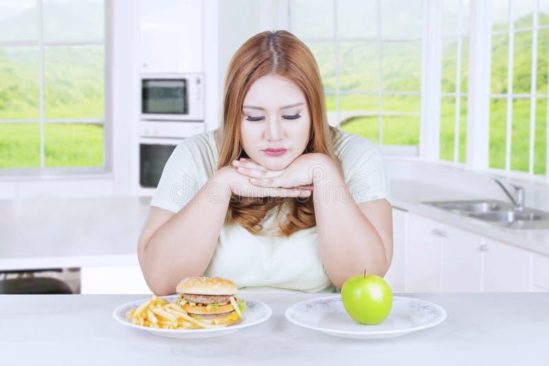 Olycklig kvinna som väljer äpplet eller hamburgaren arkivfoto