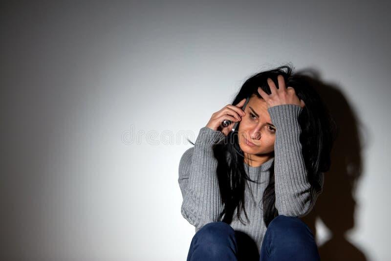 Olycklig kvinnagråt och kalla på smartphonen fotografering för bildbyråer