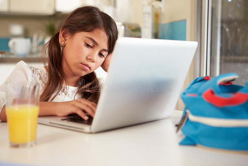 Olycklig latinamerikansk flicka som använder bärbara datorn för att göra läxa på tabellen royaltyfri foto