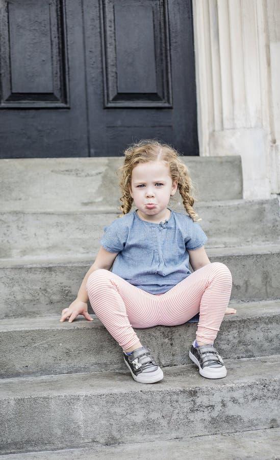 Olycklig liten flicka med sammanträde för lockigt hår på de främre momenten av hennes stads- hem royaltyfri bild