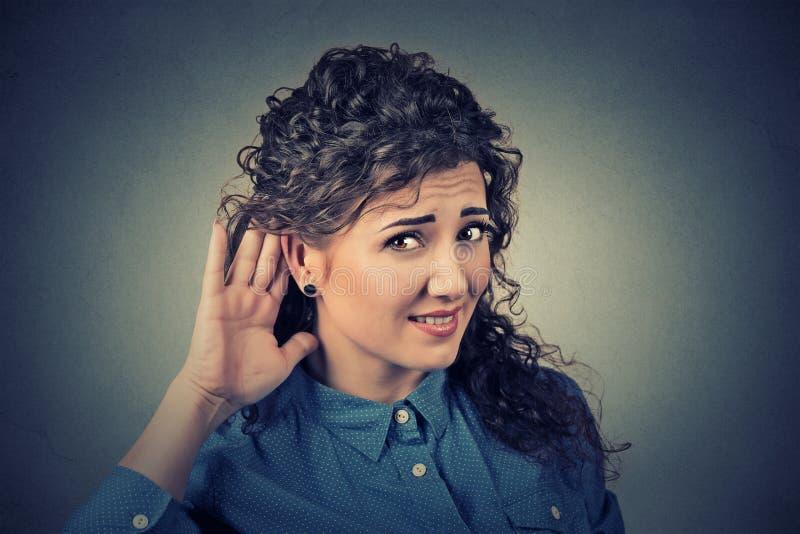 Olycklig lomhörd kvinna som förlägger handen på örat som frågar någon att tala upp royaltyfri bild