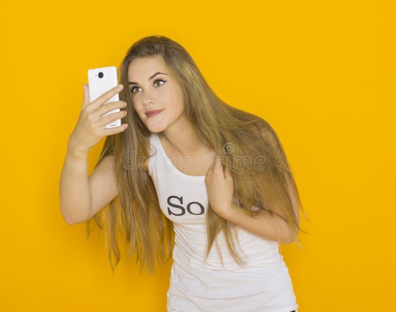 Olycklig mycket förvånad ung attraktiv kvinna något på hennes smartphone arkivfoto