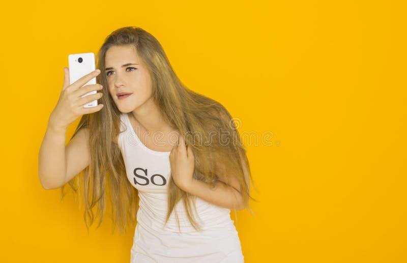 Olycklig mycket förvånad ung attraktiv kvinna något på hennes smartphone arkivbild