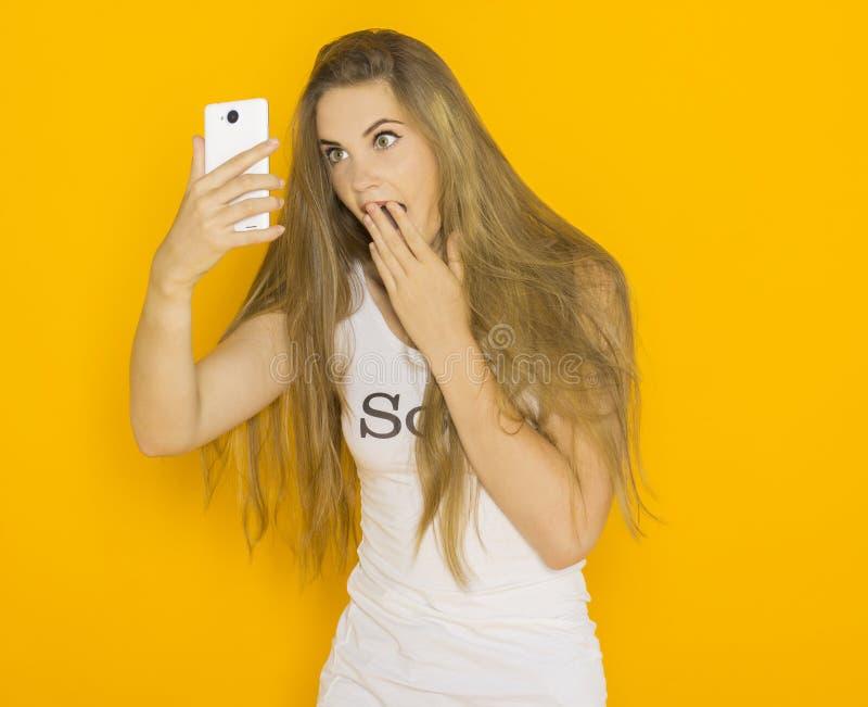 Olycklig mycket förvånad ung attraktiv kvinna något på hennes smartphone royaltyfri fotografi