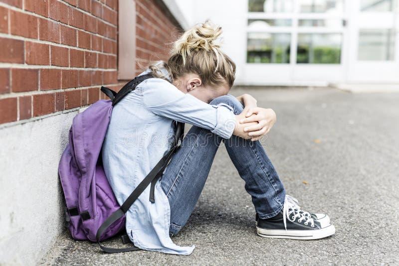 Olycklig Pre tonårig flicka på skolan arkivbilder