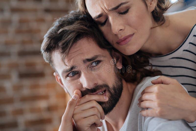 Olycklig skriande man som tröstas av hans flickvän arkivfoton