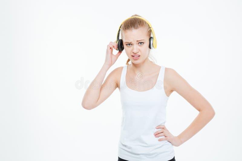 Olycklig stressad ung kvinna som tar bort gul hörlurar arkivbilder