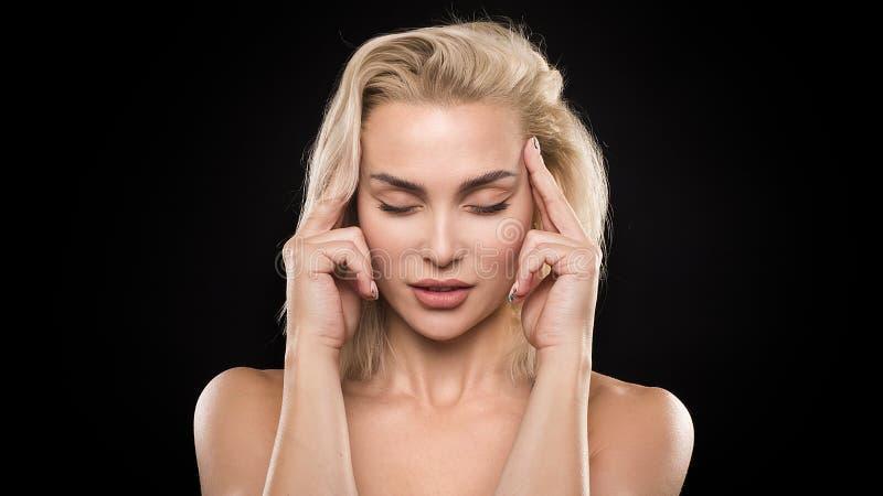 Olycklig tänkande kvinna för förvirring med huvudvärk på mörk bakgrund kvinna för closeupframsidastående royaltyfria bilder