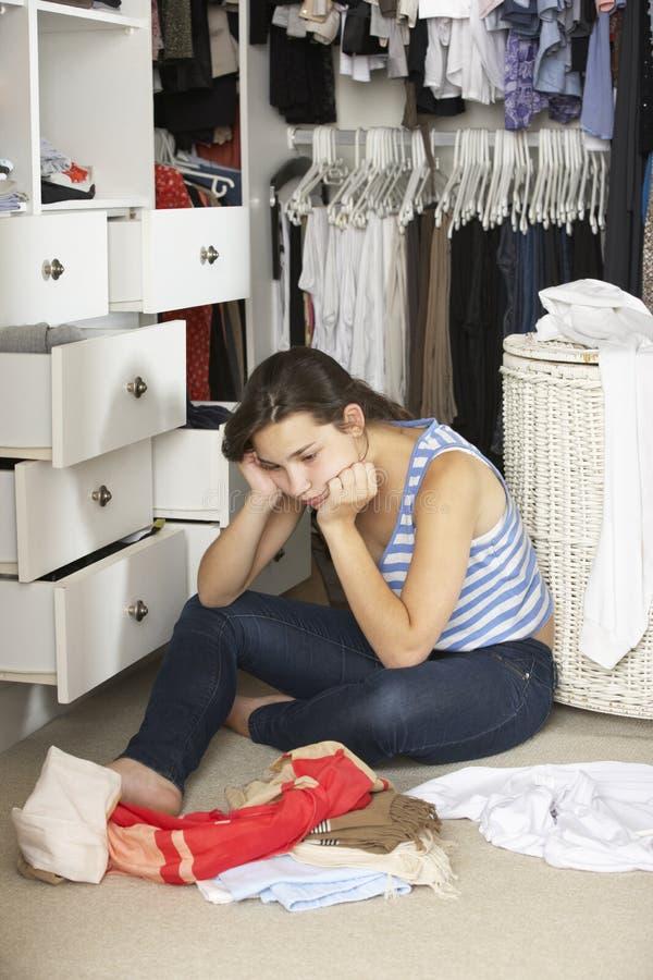 Olycklig tonårs- flicka som är oförmögen att finna den passande dräkten i garderob royaltyfri bild