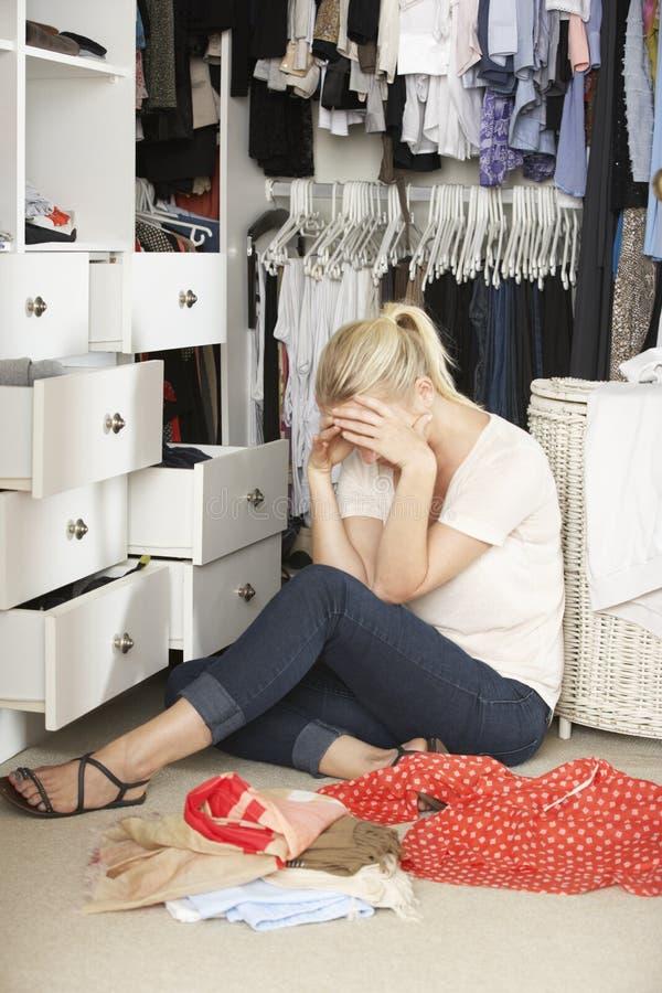 Olycklig tonårs- flicka som är oförmögen att finna den passande dräkten i garderob arkivfoton
