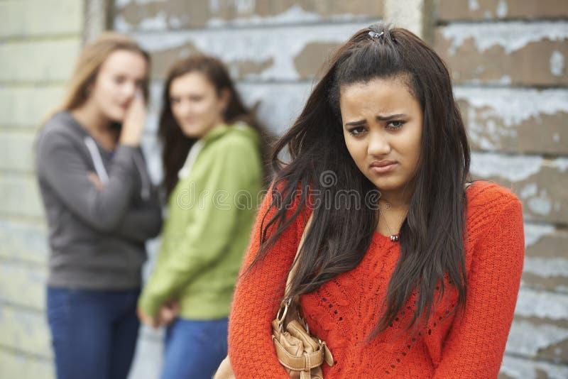 Olycklig tonårs- flicka som omkring skvallras av jämliken royaltyfri foto