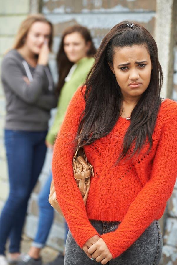 Olycklig tonårs- flicka som omkring skvallras av jämliken royaltyfri fotografi