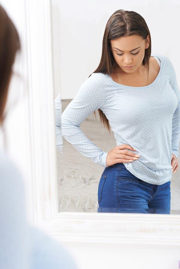 Olycklig tonårs- flicka som ser reflexion i spegel royaltyfria foton