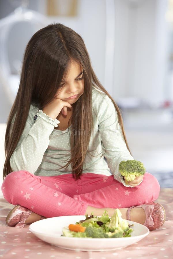 Olycklig ung flicka som kasserar plattan av nya grönsaker royaltyfria bilder
