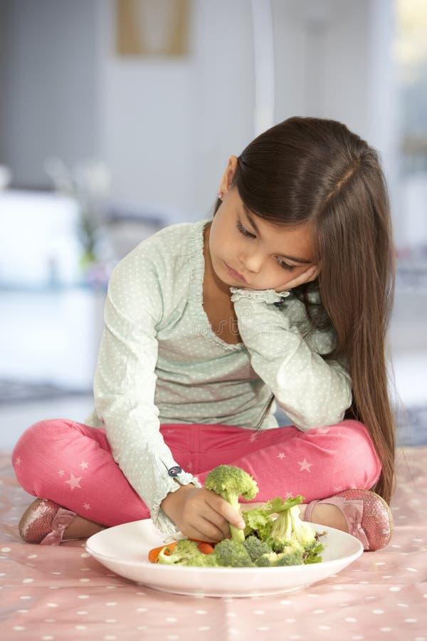 Olycklig ung flicka som kasserar plattan av nya grönsaker royaltyfri foto