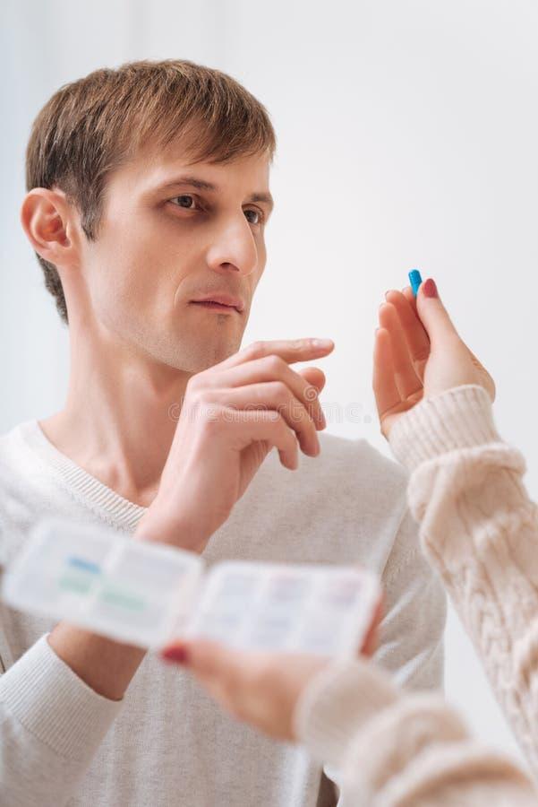 Olycklig ung man som tar en preventivpiller arkivbilder