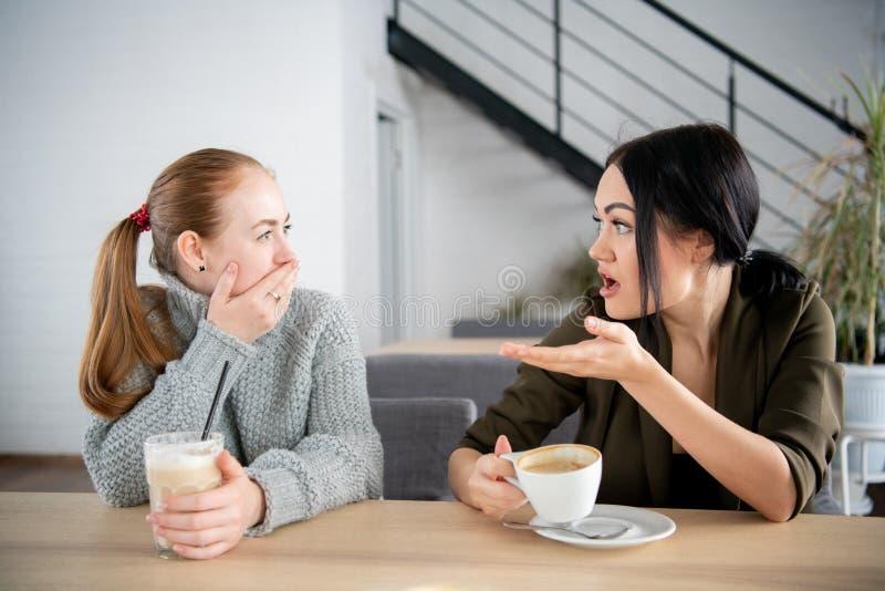 Olyckliga kvinnliga vänner diskuterar att chocka nyheterna Två chockade unga kvinnor som täcker munnen och ser de på kafét royaltyfri foto