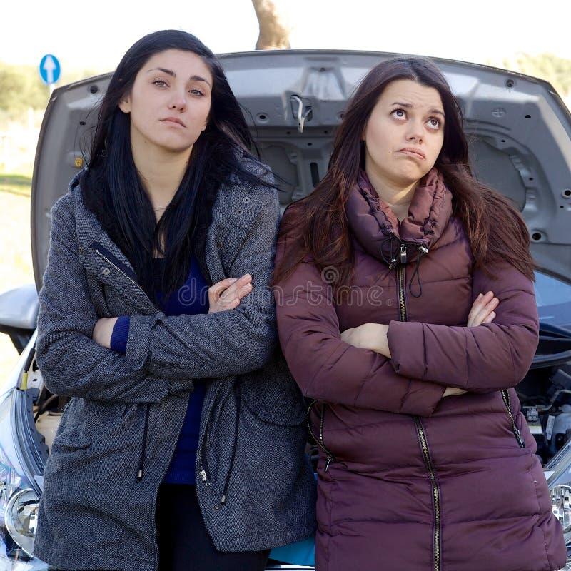 Olyckliga kvinnor som väntar på mekanikern med den brutna bilen i mitt av gatacloseupen arkivbilder
