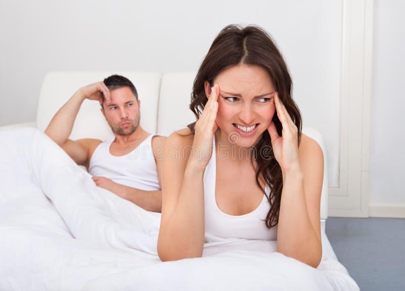 Olyckliga par på säng arkivfoto