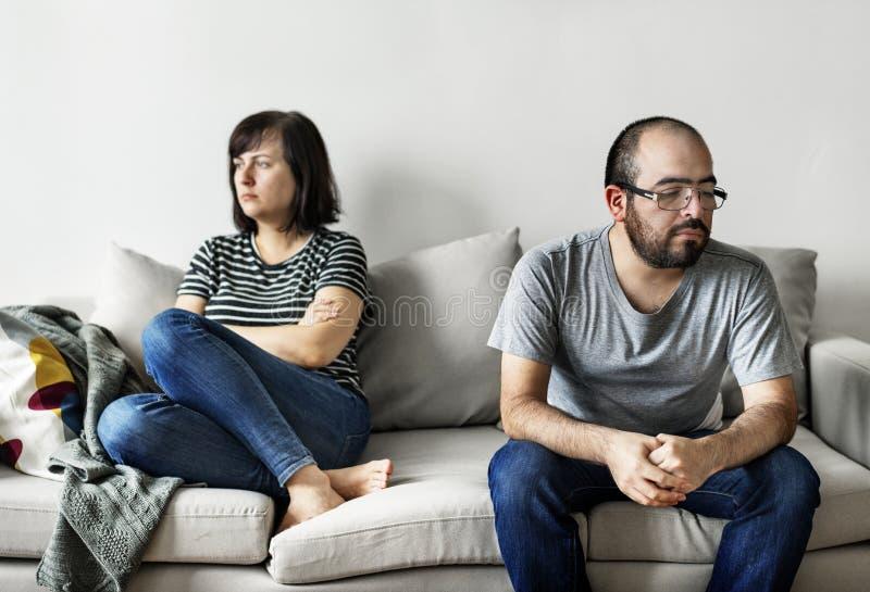 Olyckliga par som argumenterar på soffan arkivbilder