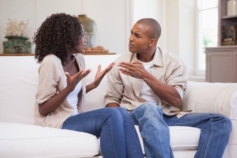 Olyckliga par som argumenterar på soffan royaltyfri bild