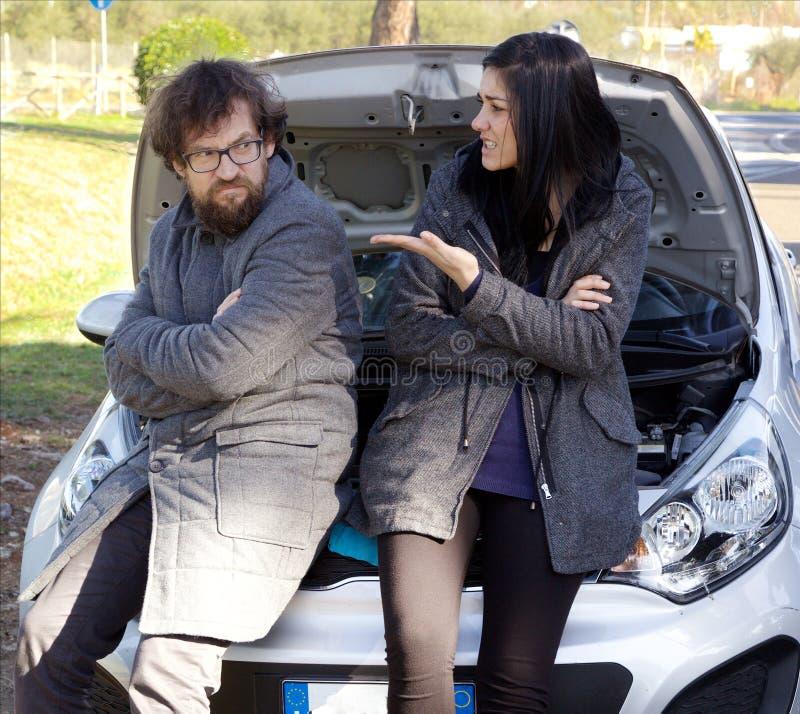Olyckliga par som framme slåss av den brutna bilen efter olycka arkivbilder