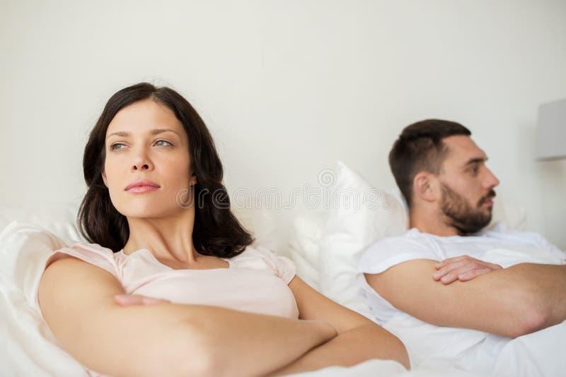 Olyckliga par som har konflikt i säng hemma royaltyfri foto