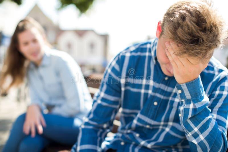 Olyckliga tonårs- par som har argument i stads- inställning arkivfoto