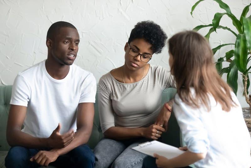 Olyckliga unga afrikansk amerikanpar som besöker psykologen royaltyfri fotografi