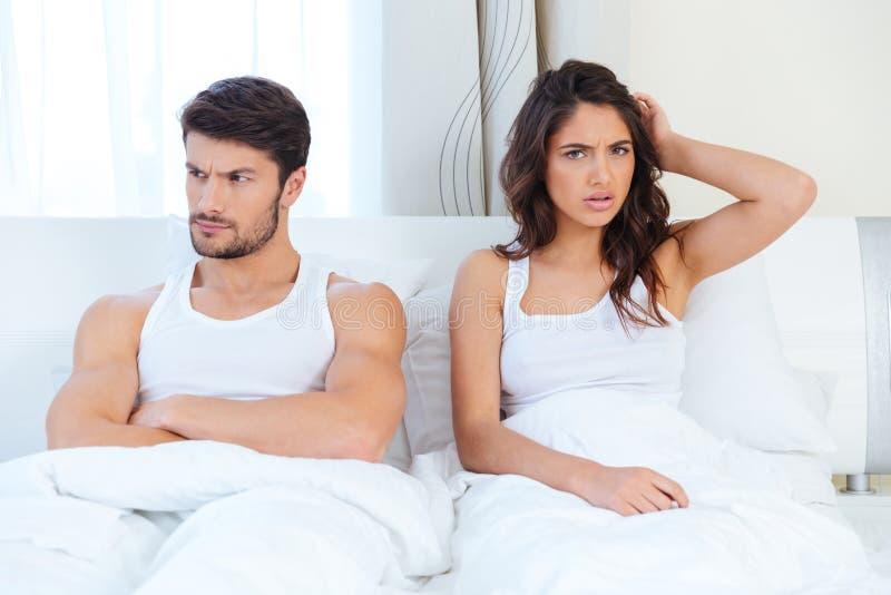 Olyckligt avskilj par som ligger i en säng arkivfoto