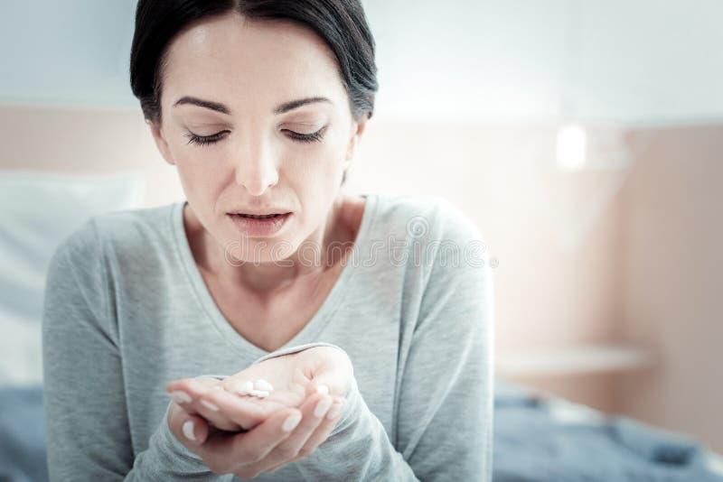 Olyckligt besviket kvinnasammanträde och hållande preventivpillerar arkivbild