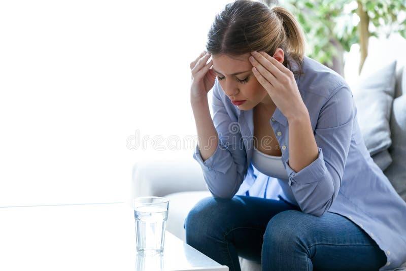 Olyckligt ensamt deprimerat sammanträde för ung kvinna på soffan hemma Fördjupningsbegrepp royaltyfri foto