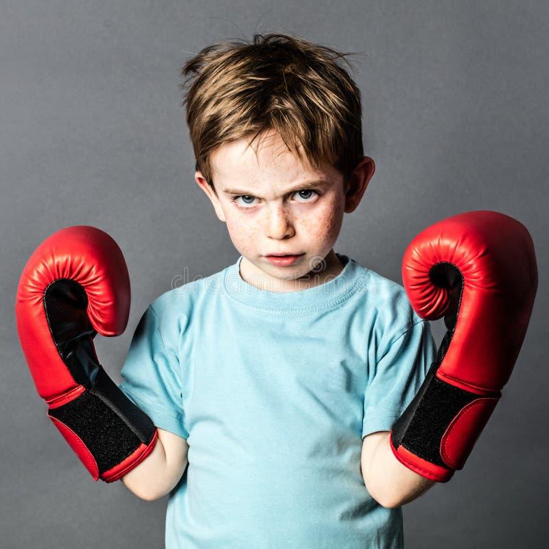 Olyckligt förskolebarn med rött hår som visar hans boxninghandskar royaltyfri bild