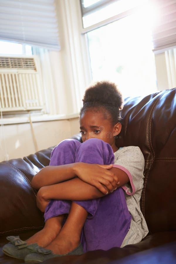 Olyckligt flickasammanträde på Sofa At Home royaltyfria bilder