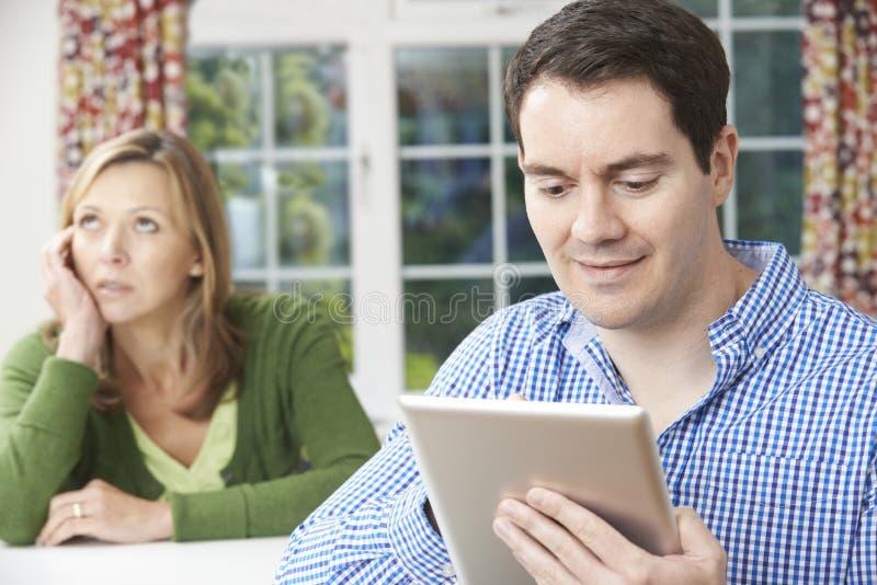 Olyckligt kvinnasammanträde på tabellen som partner använder den Digital minnestavlan fotografering för bildbyråer